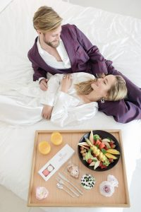 couple laying in bed having breakfast